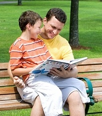 Boy sitting on his dad's lap as he reads to him